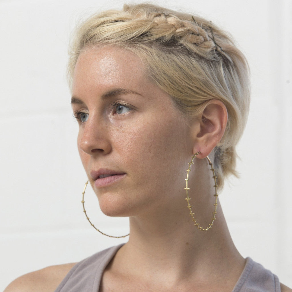 "Model wear 3.25"" lightweight bronze hoops with small spherical details running along both sides. Made with gold ear wires to protect those sensitive to base metal."