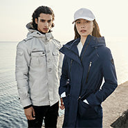 Man and woman stands on edge of pier near water. Man on left wears Fisherman men's shirt jacket in Light Grey colour. Woman on left wears Ines ladies raincoat in Marine colour.