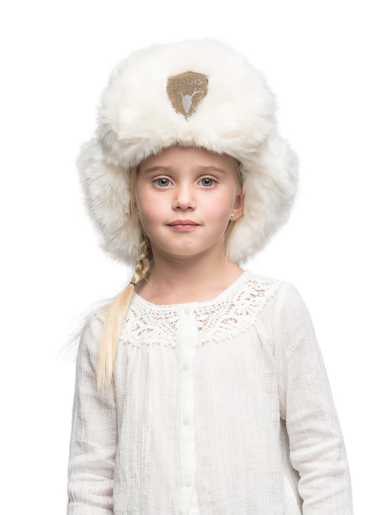 Plush white faux fur trapper hat with a khaki suede Nobis patch on the front of the brim