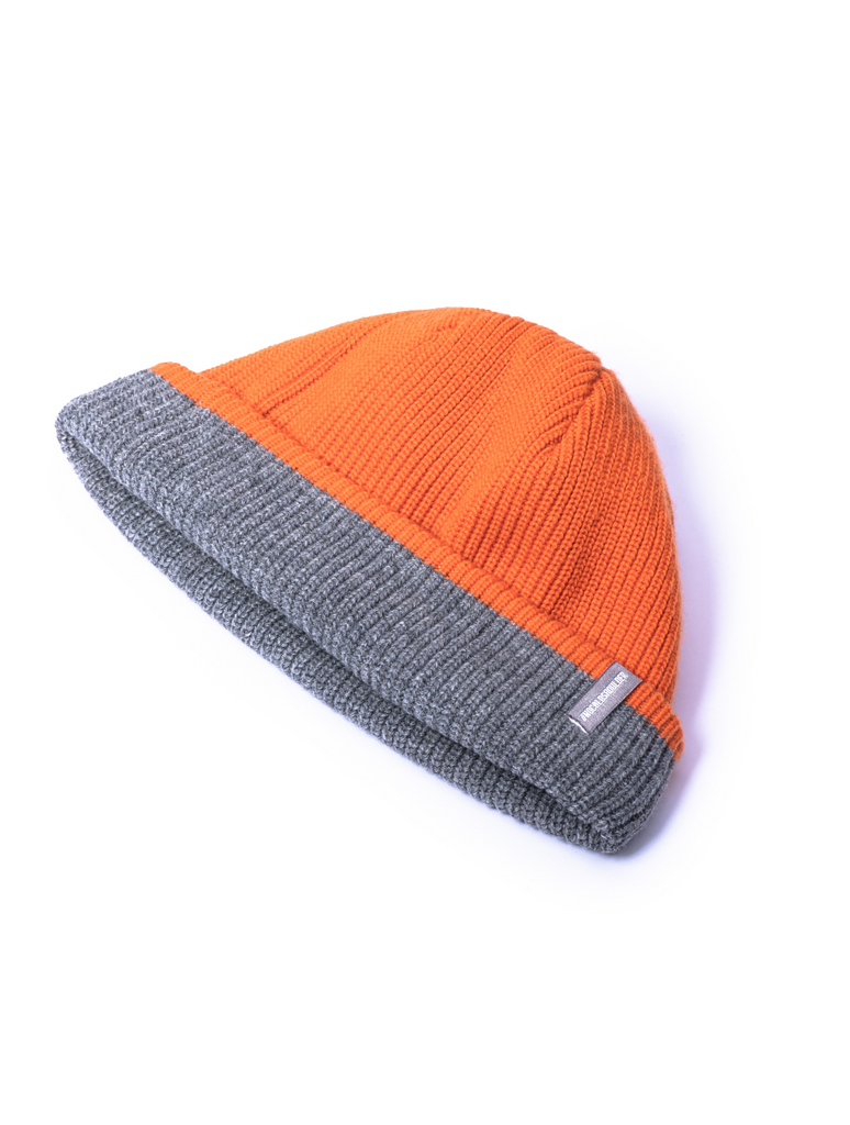 Knitted reversible beanie with orange side displayed.| color