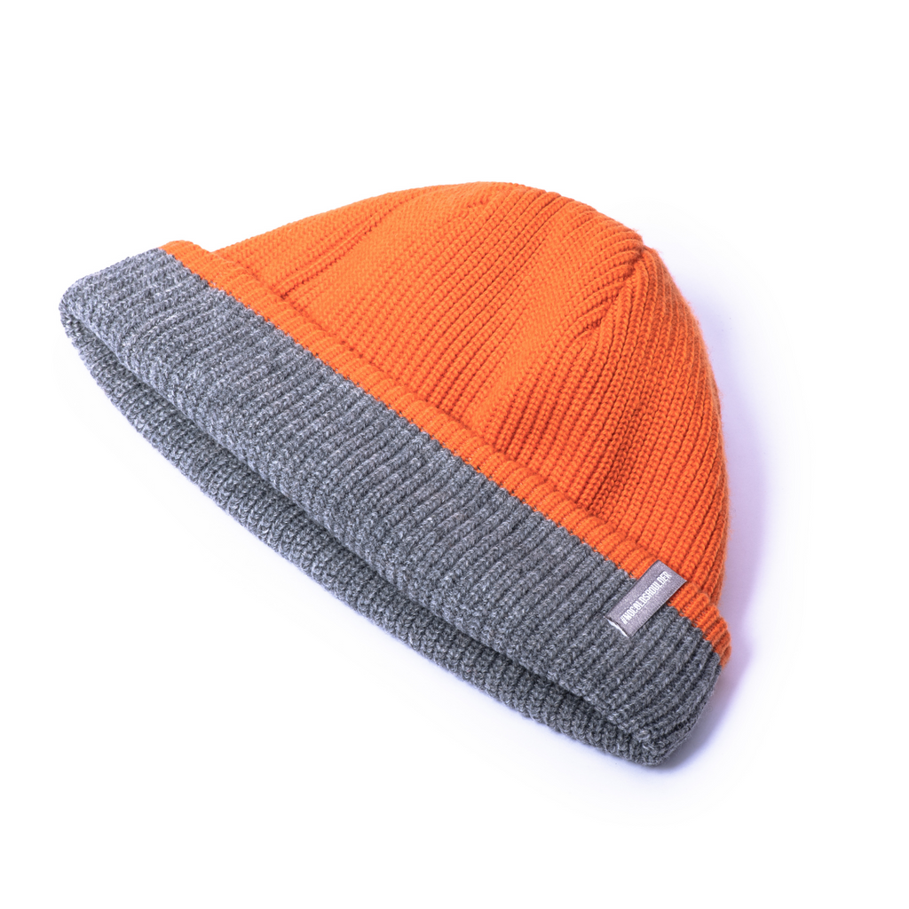 Knitted reversible beanie with orange side displayed. | color
