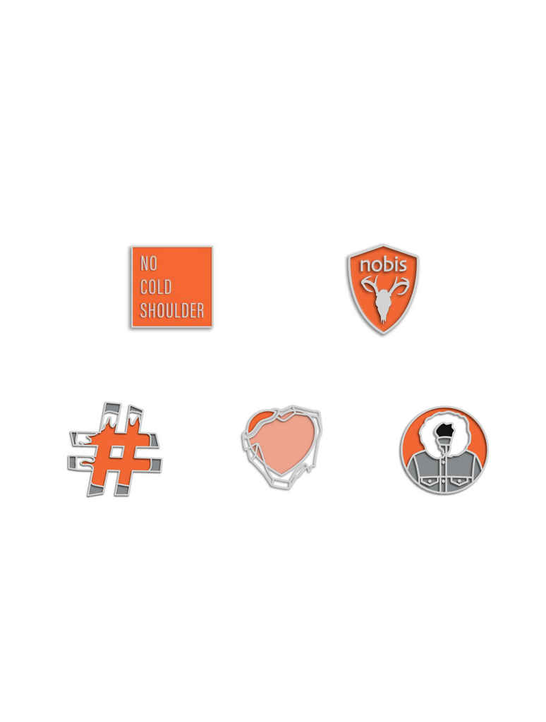 Set of five enamel pins that include an orange square with no cold shoulder printed in the center, and orange nobis logo shield, and orange and grey hashtag, an orange heart with ice over it and a Atomic and grey circle parka Pin Pack| color