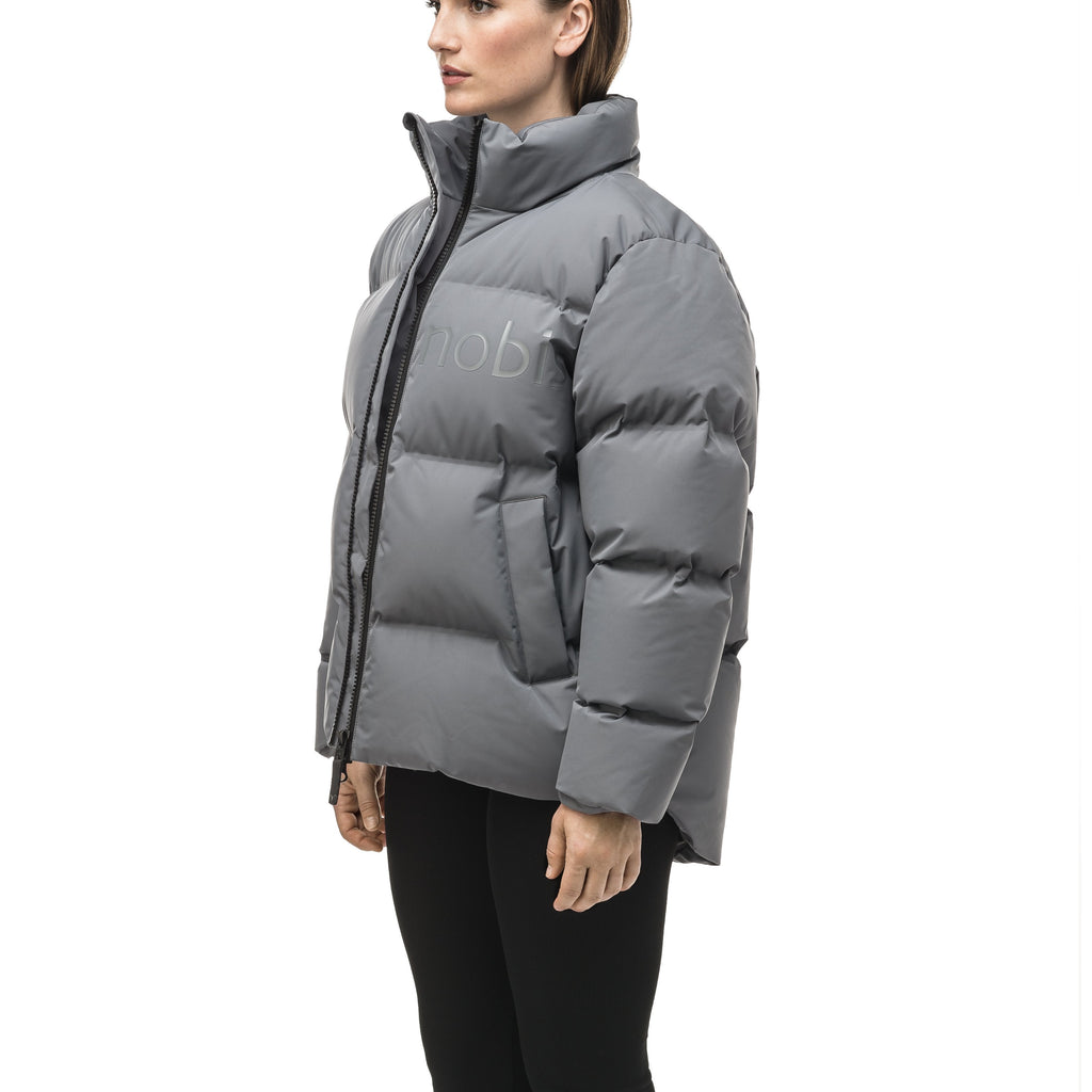 Women's puffer jacket with a minimalist modern design; featuring graphic details like oversized tonal branding, an exposed zipper, and seamless puffer channels to lock in the Premium Canadian Origin White Duck Down in Concrete color | color