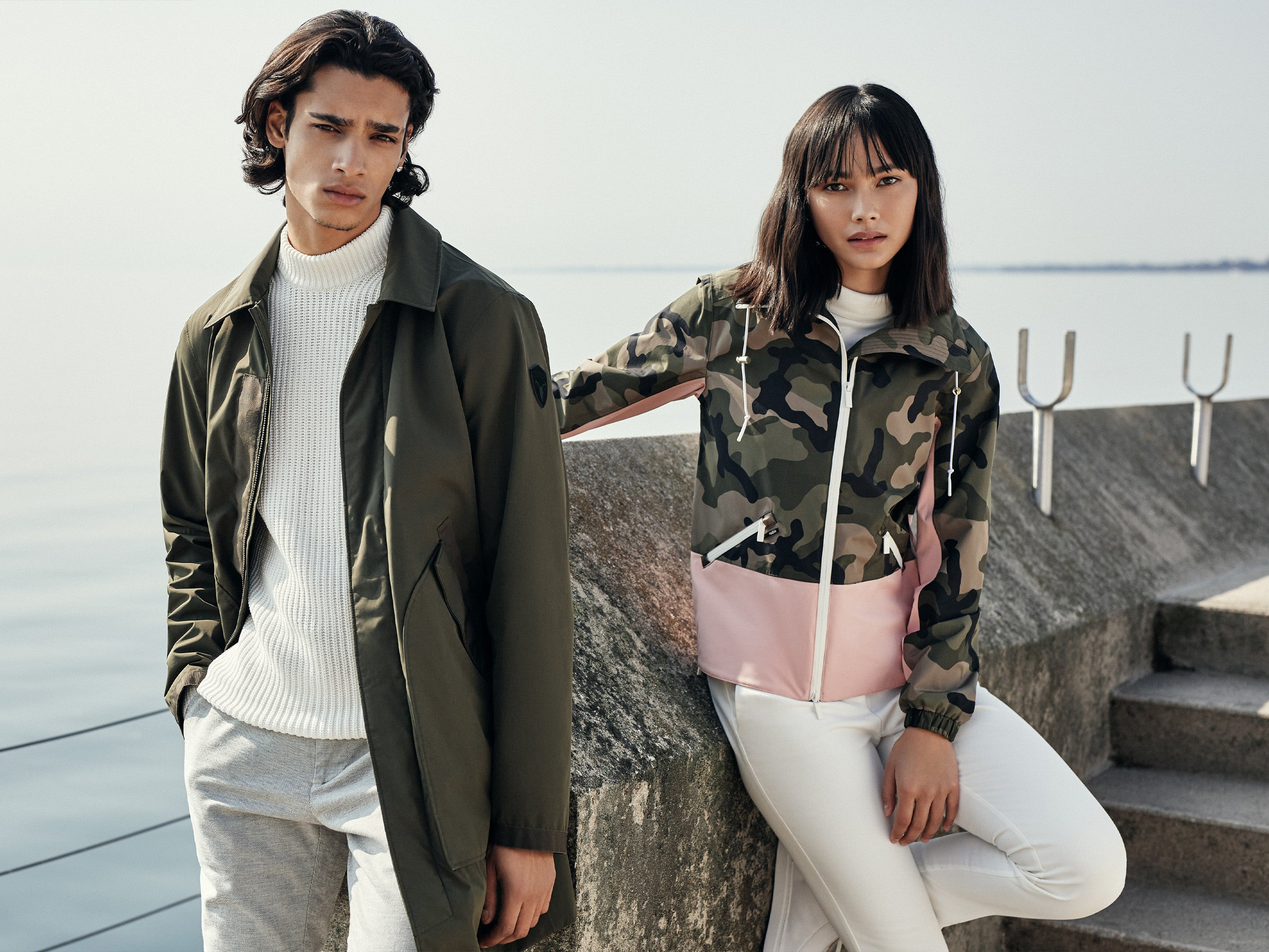 Man stands and woman leans on the edge of a pier. Man wears Yardley men's raincoat in Fatigue colour, woman wears Leah ladies tech jacket in Camo colour.