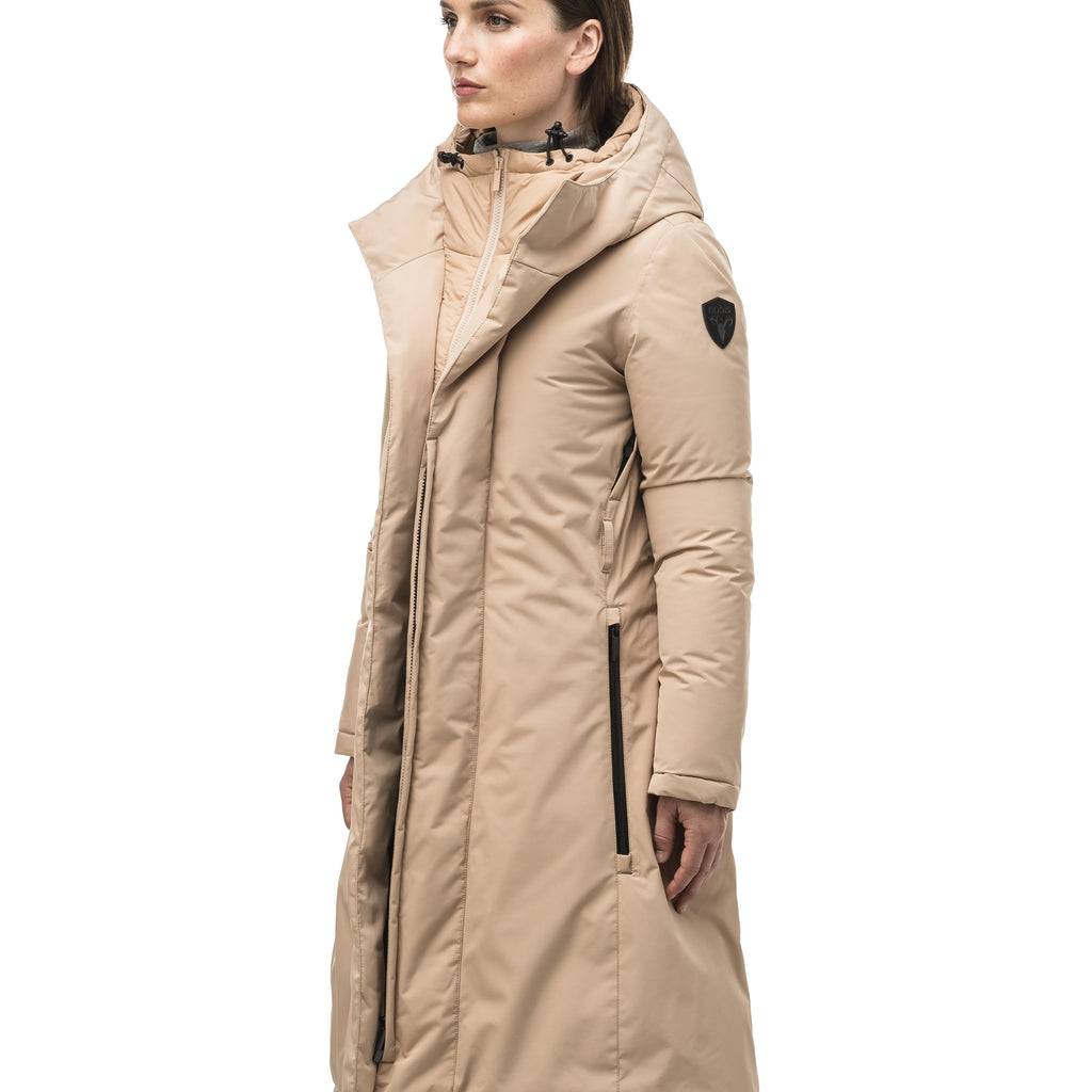 Long calf length hooded women's winter parka with an inner hip length closure, exterior hem length zipper and magentic placket in Fawn | color