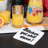 "Lifestyle photography image in a mimosa setting, featuring our white cocktail napkin with black design that reads ""Bitches Get Shit Done!"""