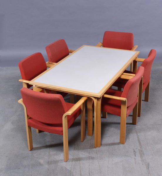 Beech Dining Table with White Surface and Six Beech Armchairs with Red Fabric Seats and Backs by Rud Thygesen and Johnny Sorensen