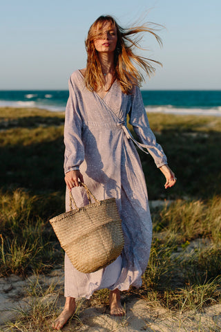 soft grey wrap dress model holding seagrass bag