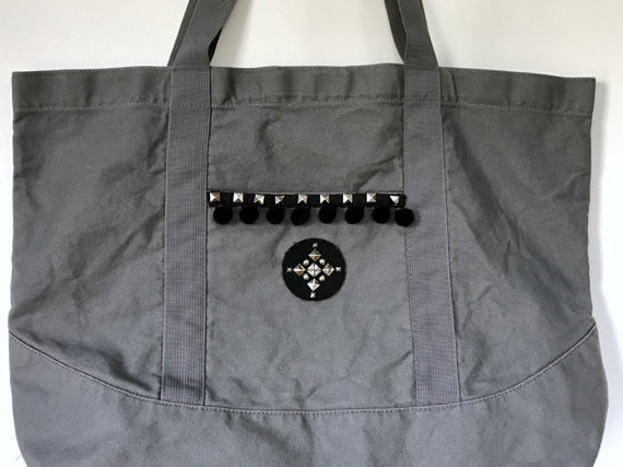 gray cotton canvas tote bag with studded leather patch and pom pom trim
