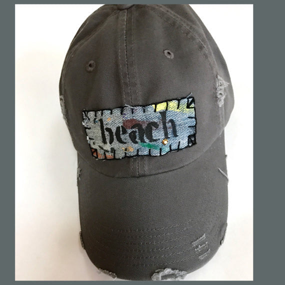 "distressed gray adjustable cap with hand-painted denim patch that says ""beach"""