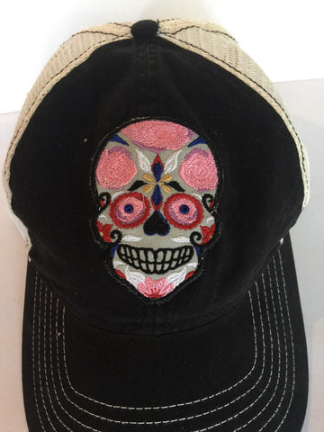 Black snapback trucker style cap with custom sugar skull embroidered patch