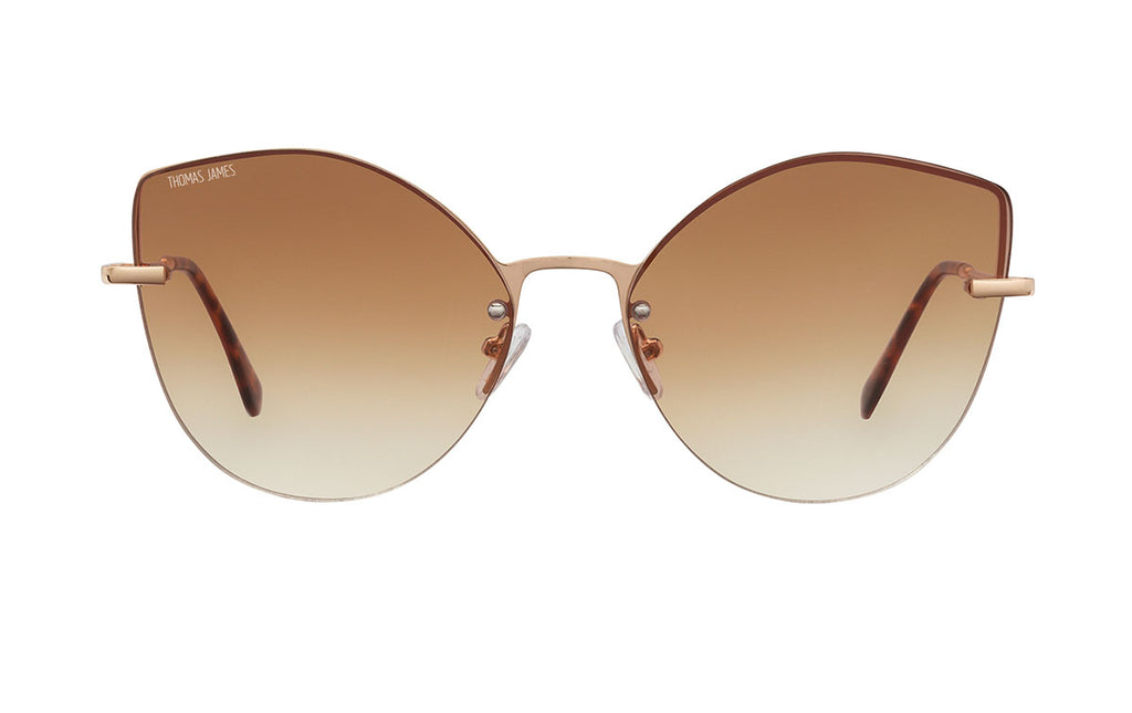 01-Cacao: Rimless round gold cat eye frame with small gold detailing on the gradient brown UV400 lens.