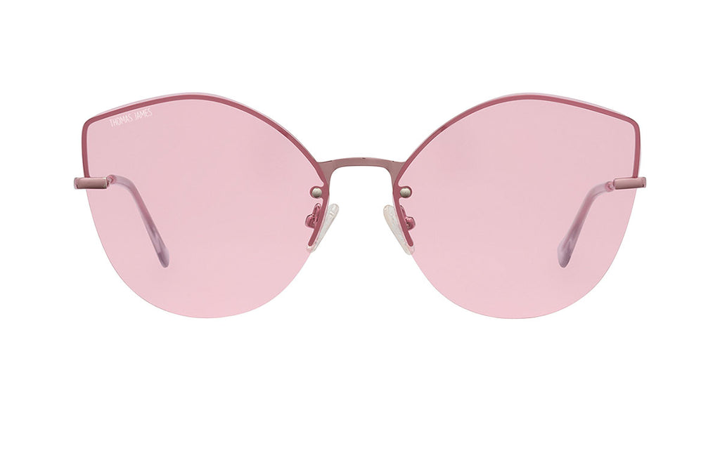 02-Sugar: Rimless round pink cat eye frame with small shiny pink detailing on the transparent pink UV400 lens