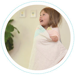 toddler with quilt wrapped around her looking cozy