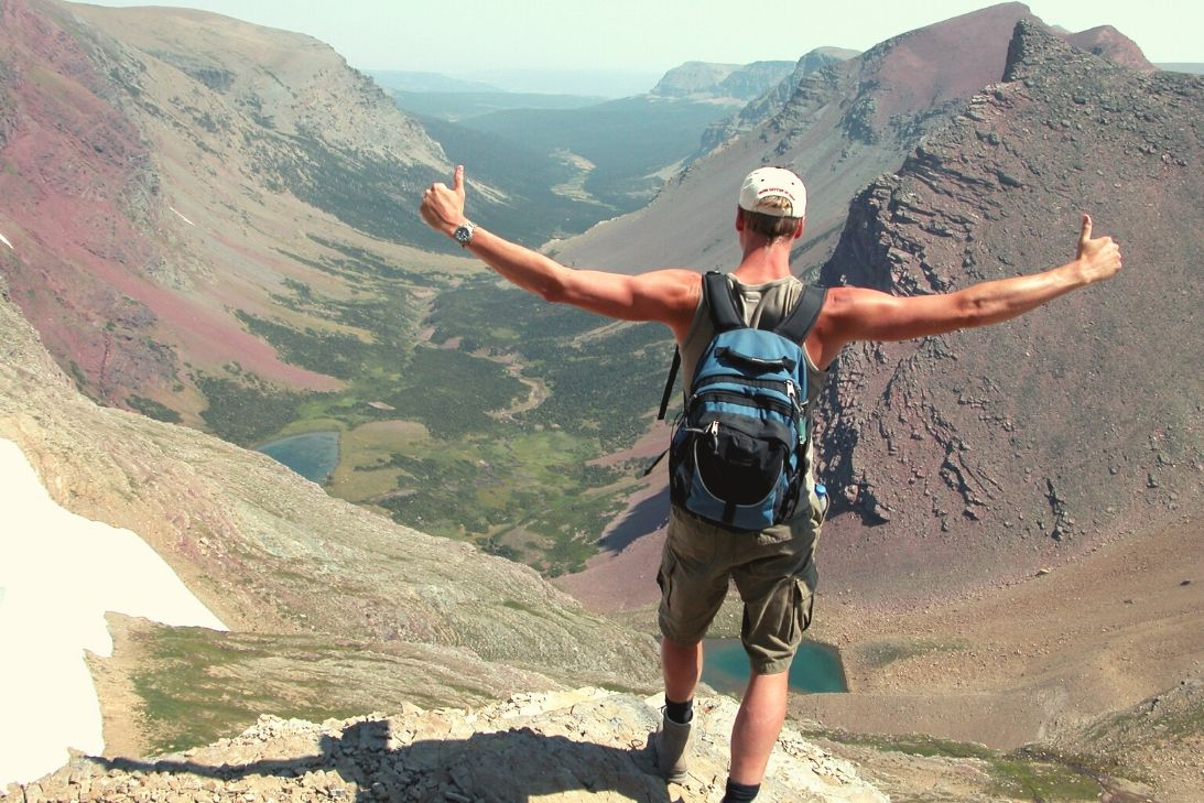 A man standing in a victorious pose in a mountain range.