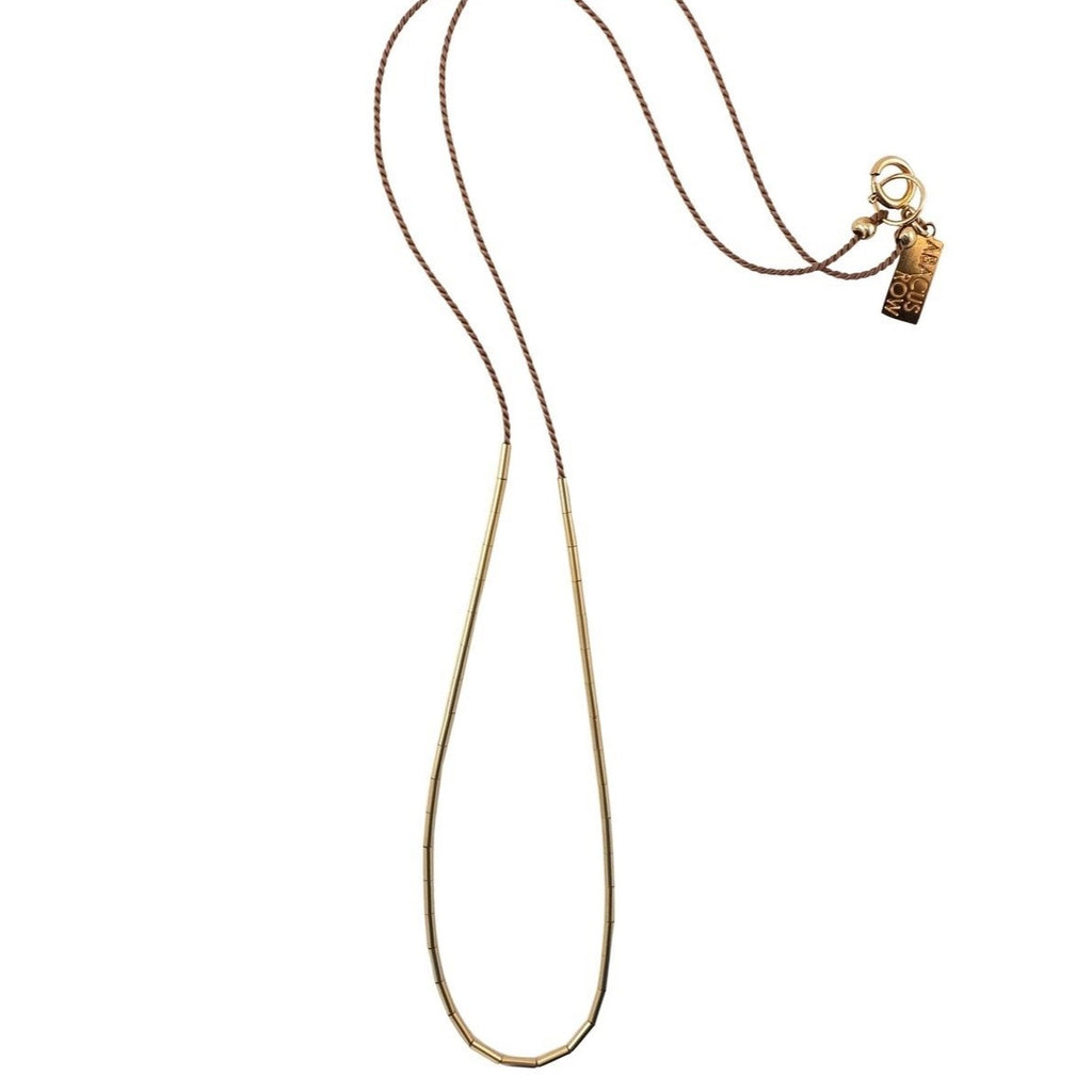 The Circinus is simple and elegant with a dash of color and gold. The tubes on this necklace can be redistributed to create a continuous arc or a smattering of gold by gently moving the beads around where you want them placed.