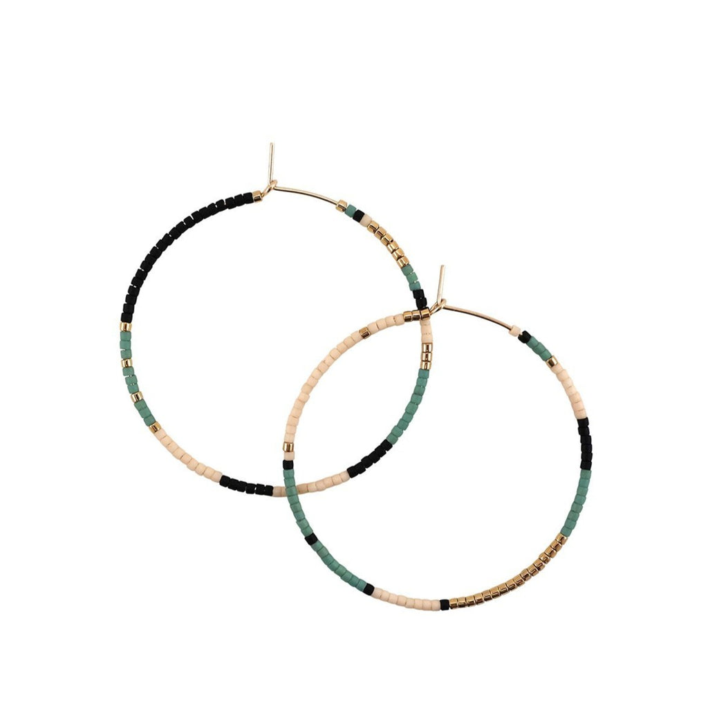 With Abacus Row's Tanami Hoops, designer Christina Trac plays with fixed and open pattern designs. Each earring hoop is hand hammered from 14k gold-filled wire and beaded by hand. These large hoops are whisper light for everyday adornment. Oasis