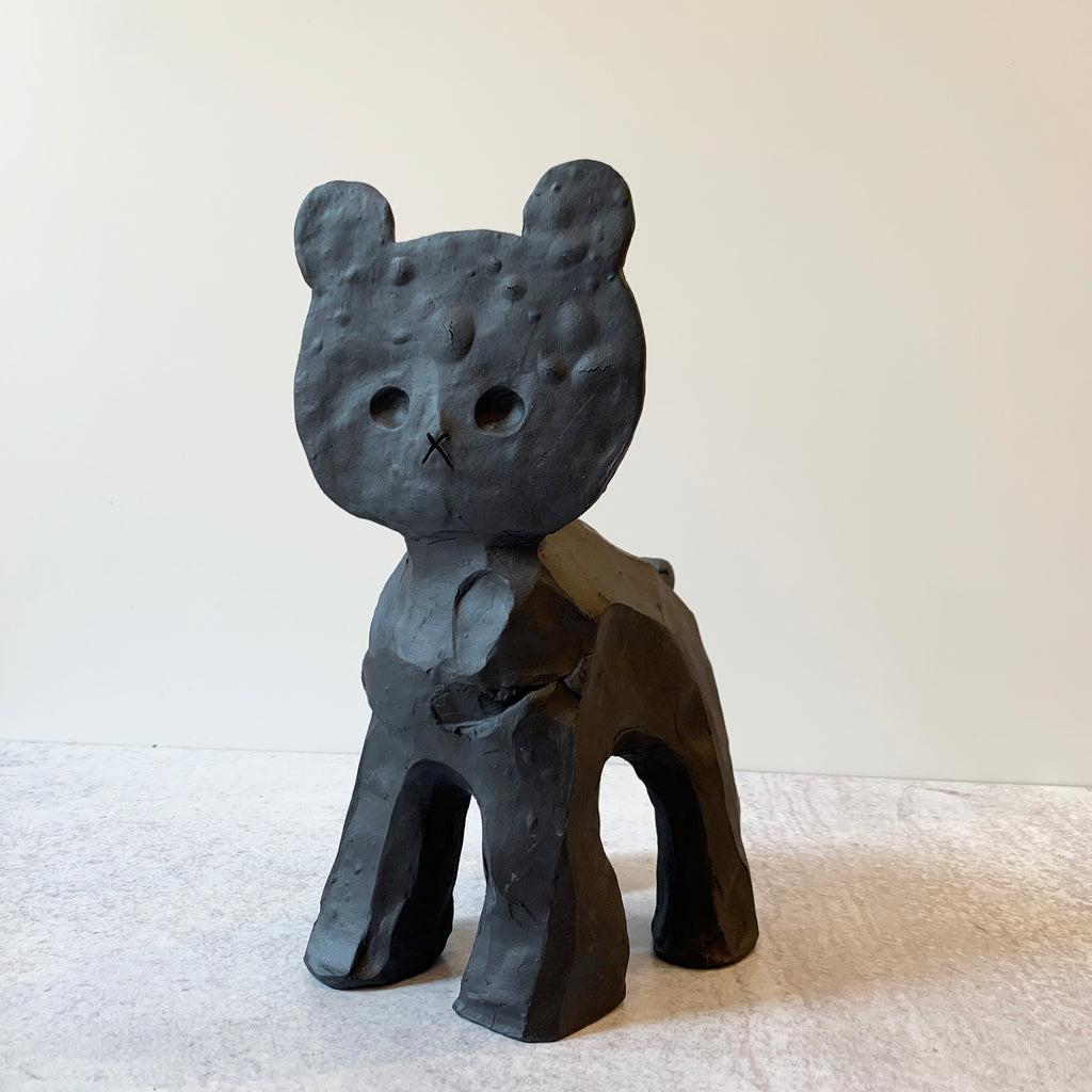 Flat Head Bear captures Austyn Taylor's humorous outlook on animist history, and pop culture (flattened cartoon characters) sculpted in a very black, ebony-like finish using Aardvark Clay's Cassius Basaltic. Front view