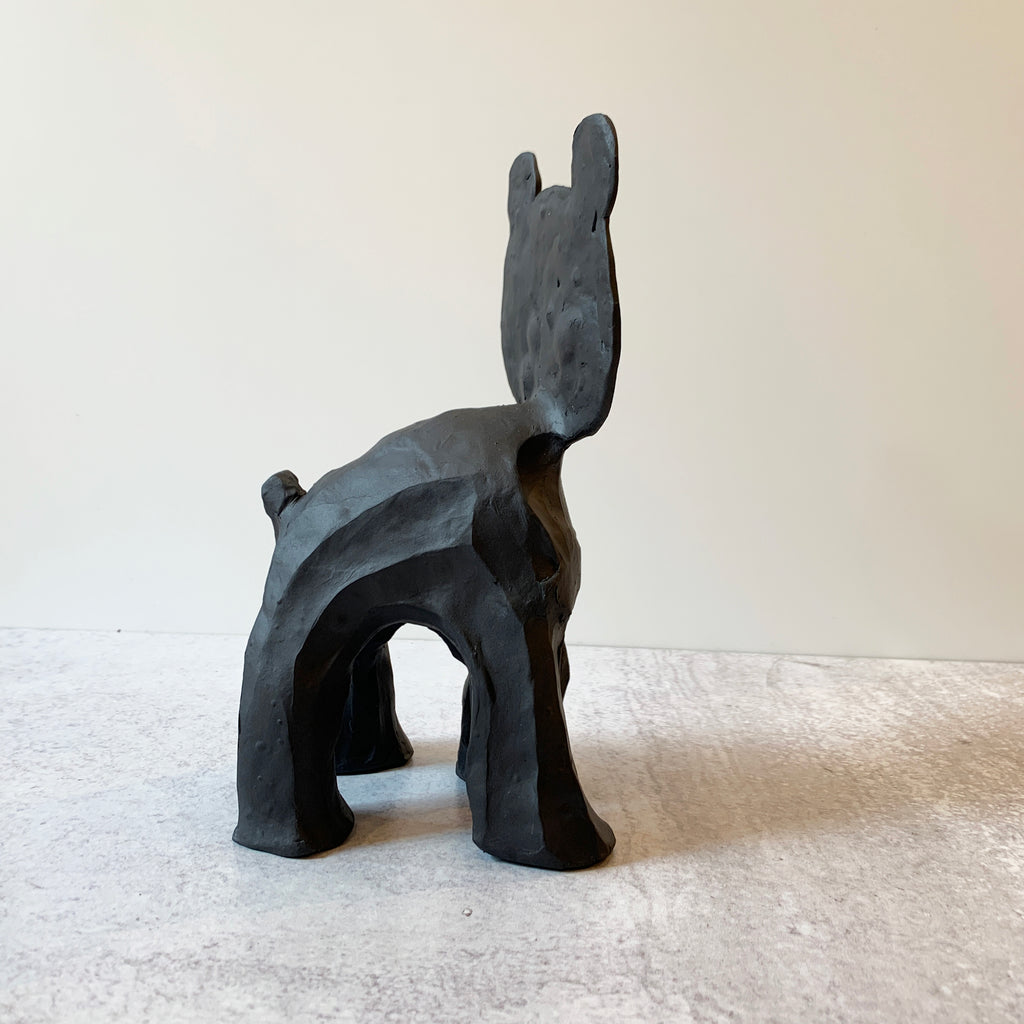 Flat Head Bear captures Austyn Taylor's humorous outlook on animist history, and pop culture (flattened cartoon characters) sculpted in a very black, ebony-like finish using Aardvark Clay's Cassius Basaltic. Side View