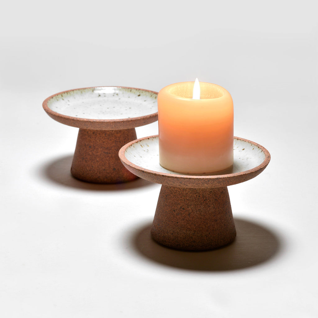 Elevate candles (so guests are always in the most flattering light) and keep wax off your table at the same time with these Birch White ceramic candle stands by Bob Dinetz.