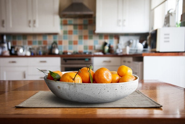 The large low serving bowl in satin white glaze delivers a beautiful foundation for salads, shared pasta, grilled vegetables and fresh fruit. Shown in environment.