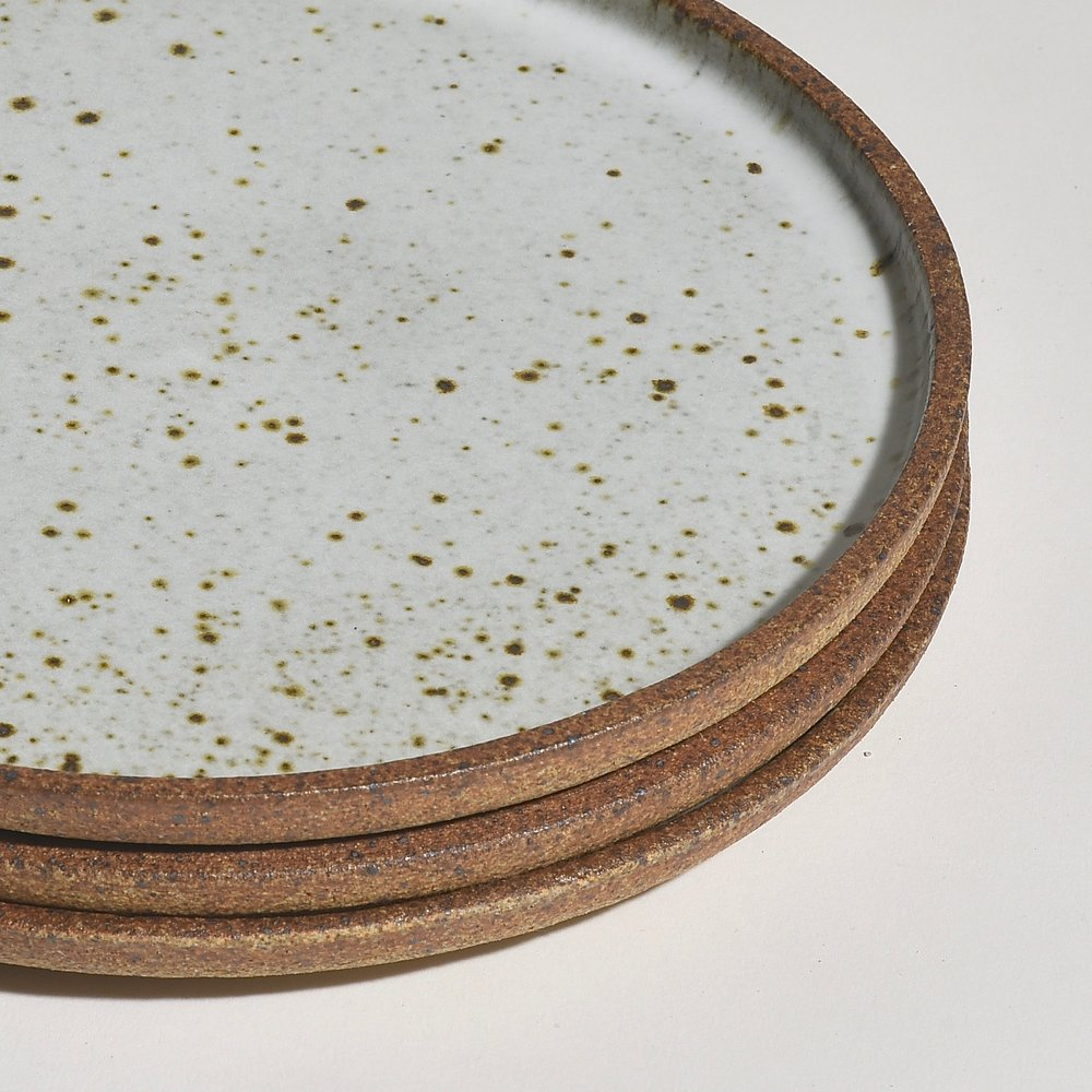 These plates are wheel-thrown and glazed in Birch White while the unglazed exterior, or underside, has a wonderful roasted almond color providing a beautiful contrast to the glazed top surface. Iron in the clay produces the speckles in the surface—the amount varies with each plate. Shown stacked.