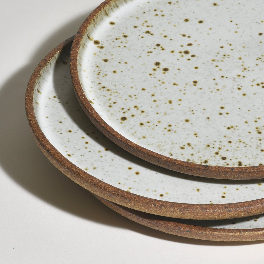 These plates are wheel-thrown and glazed in Birch White while the unglazed exterior, or underside, has a wonderful roasted almond color providing a beautiful contrast to the glazed top surface. Iron in the clay produces the speckles in the surface—the amount varies with each plate. Stack shown with variations in speckles.