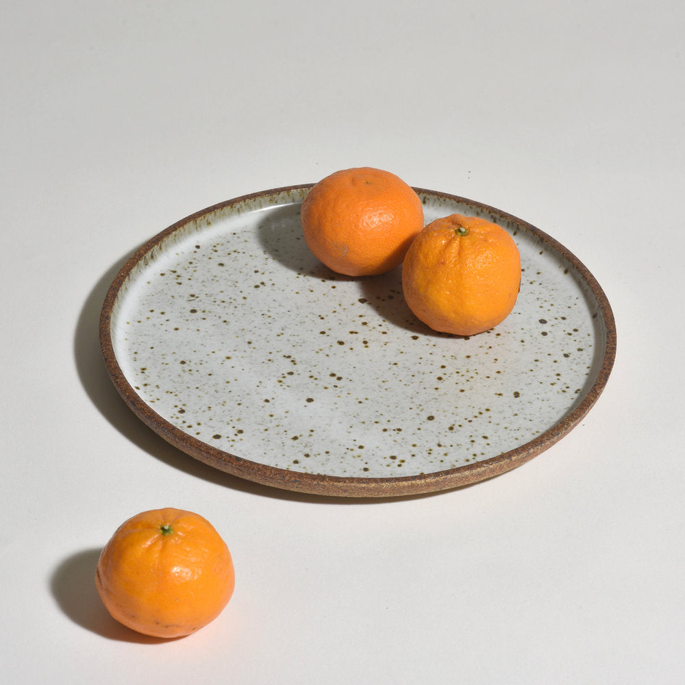 These plates are wheel-thrown and glazed in Birch White while the unglazed exterior, or underside, has a wonderful roasted almond color providing a beautiful contrast to the glazed top surface. Iron in the clay produces the speckles in the surface—the amount varies with each plate. Shown with tangerines.