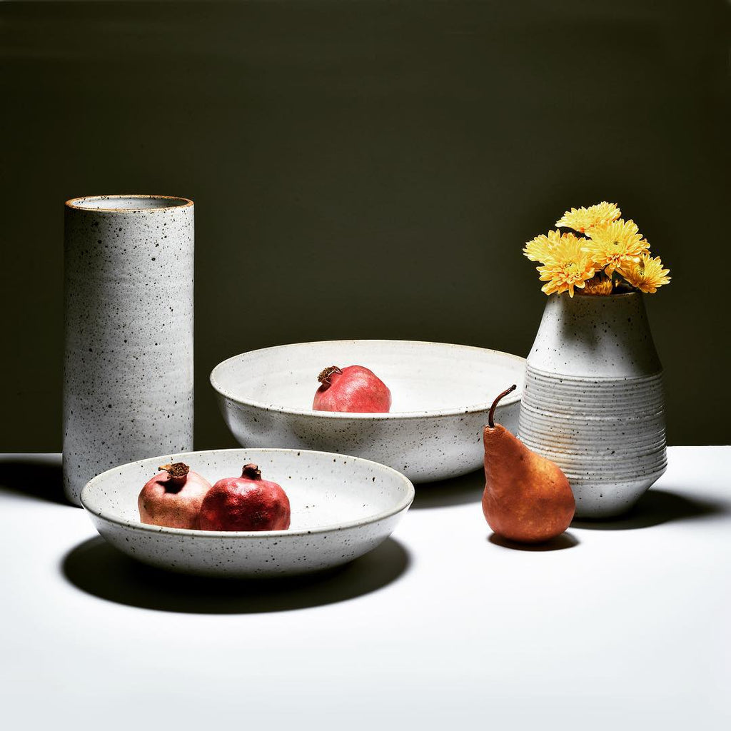The large low serving bowl in satin white glaze delivers a beautiful foundation for salads, shared pasta, grilled vegetables and fresh fruit. Shown with a larger bowl, container vase, and flower vase.