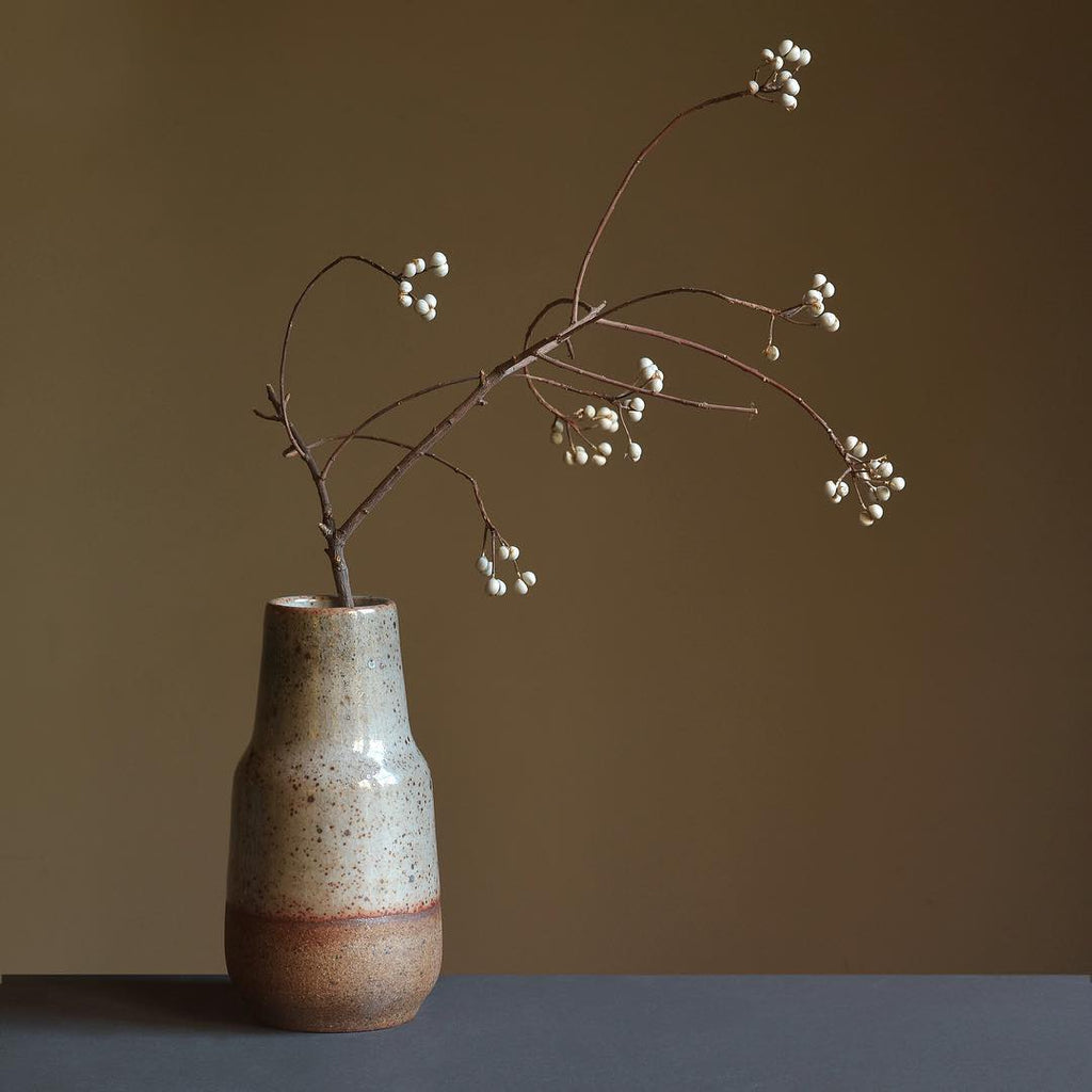 The Step Vase is an elegant vessel for a flower bouquet, tree branch or decorative item on its own. We also love using it to serve Saké. We love the naked clay at the base. Shown with tree branch.