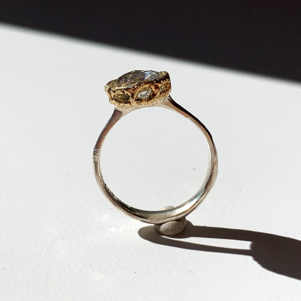 This is a cut crystal ring featuring a 14k gold lace frame and silver etched bottom with a smooth band.