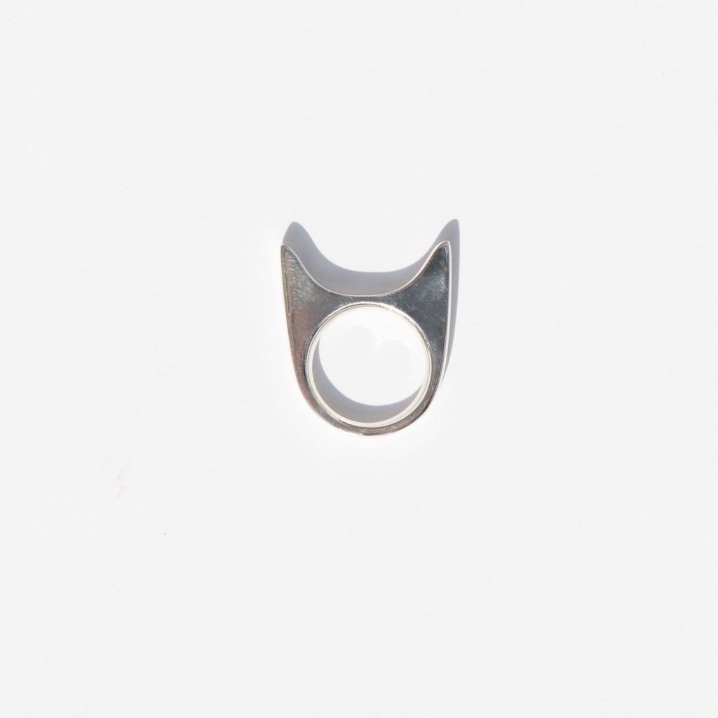 "This sly kitten of a ring is brilliantly designed for a stealthy fit on your ring, middle, or index finger. Rather than wearing it with the ""ears"" upright, the suggested wear is to turn it sideways so that a finger fits between the ears of the kitten to lay as a simple, sleek bar across the fingers. Sneaky kitty."