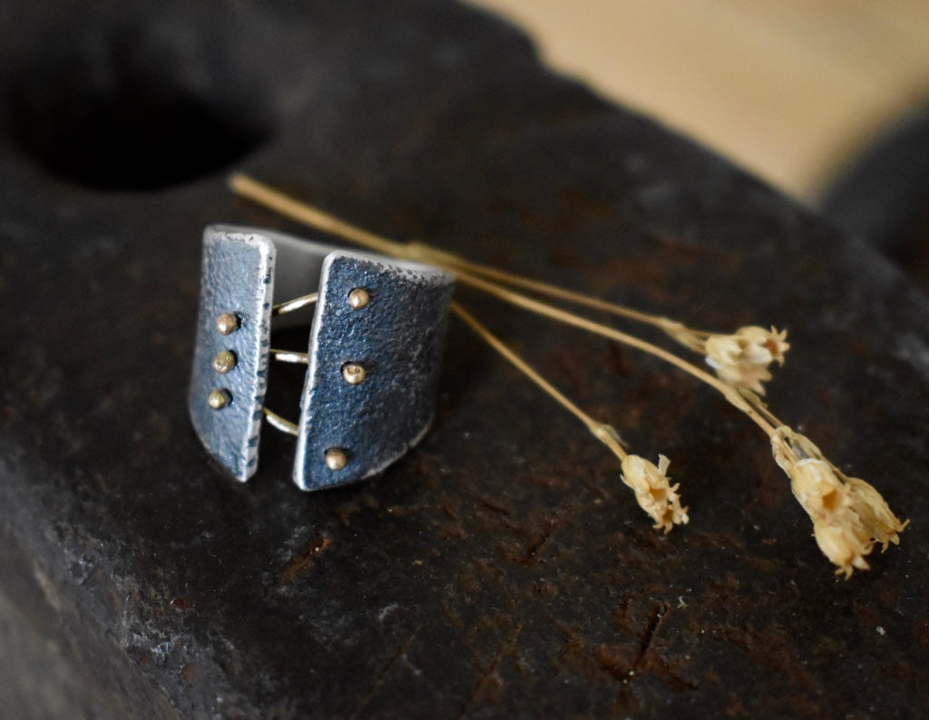 We love Esther Metal's Binding Light collection, with its corseted use of 14k torch formed rivets that bind the oxidized silver ring.