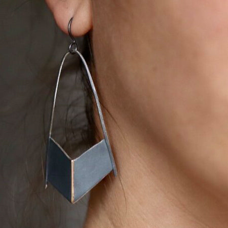 Esther fabricated these earrings to inspire the wearer to feel strength and protection. Their shield-like shape is made using oxidized sterling silver with a 14K yellow gold center seam. Shown on model.