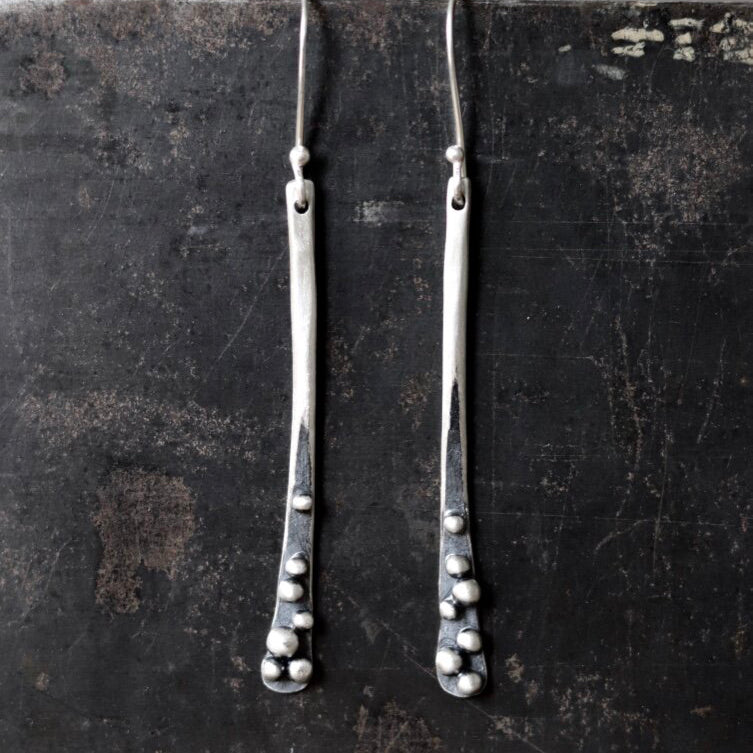 These long sprout earrings in sterling silver by Esther Metals are sublime for day to night with their oxidized granulation seed orbs settled at the base.