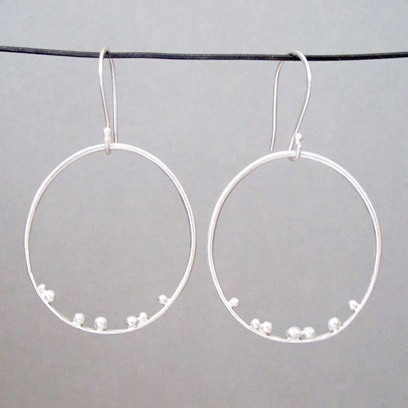 These large hoop earrings in sterling silver by Esther Metals will be your daily go-to with their delicately placed seed orbs.