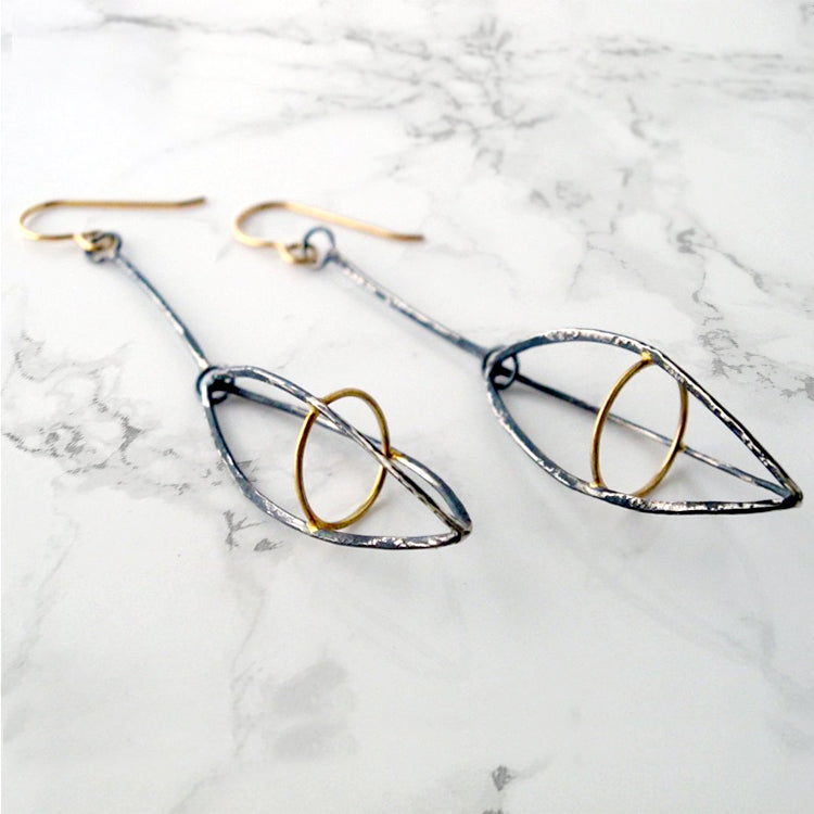 These dramatic earrings hold the Earth within the atmosphere or your inner thoughts among the cosmos. We love how the gold details pop in contrast to the oxidized silver.
