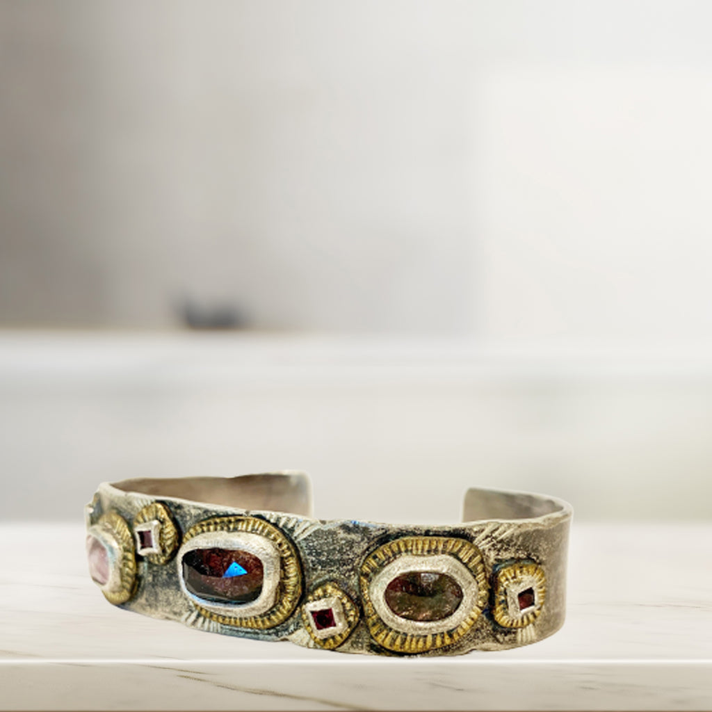 An absolute stunner on your wrist. Wear it on its own or layer it for dramatic emphasis. This cuff is hand-formed of fine silver, bronze, and natural ethically sourced tourmalines in shades of pink and coral.