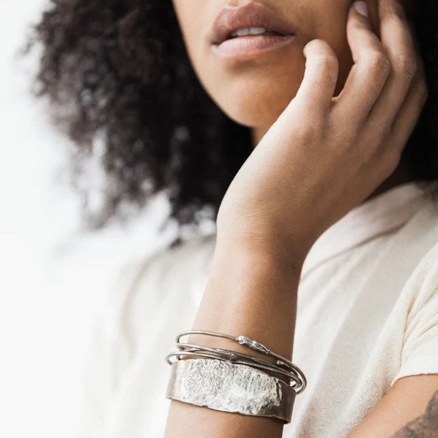 Jacqueline unisex cuff by Franny E of fine silver and bronze on model.