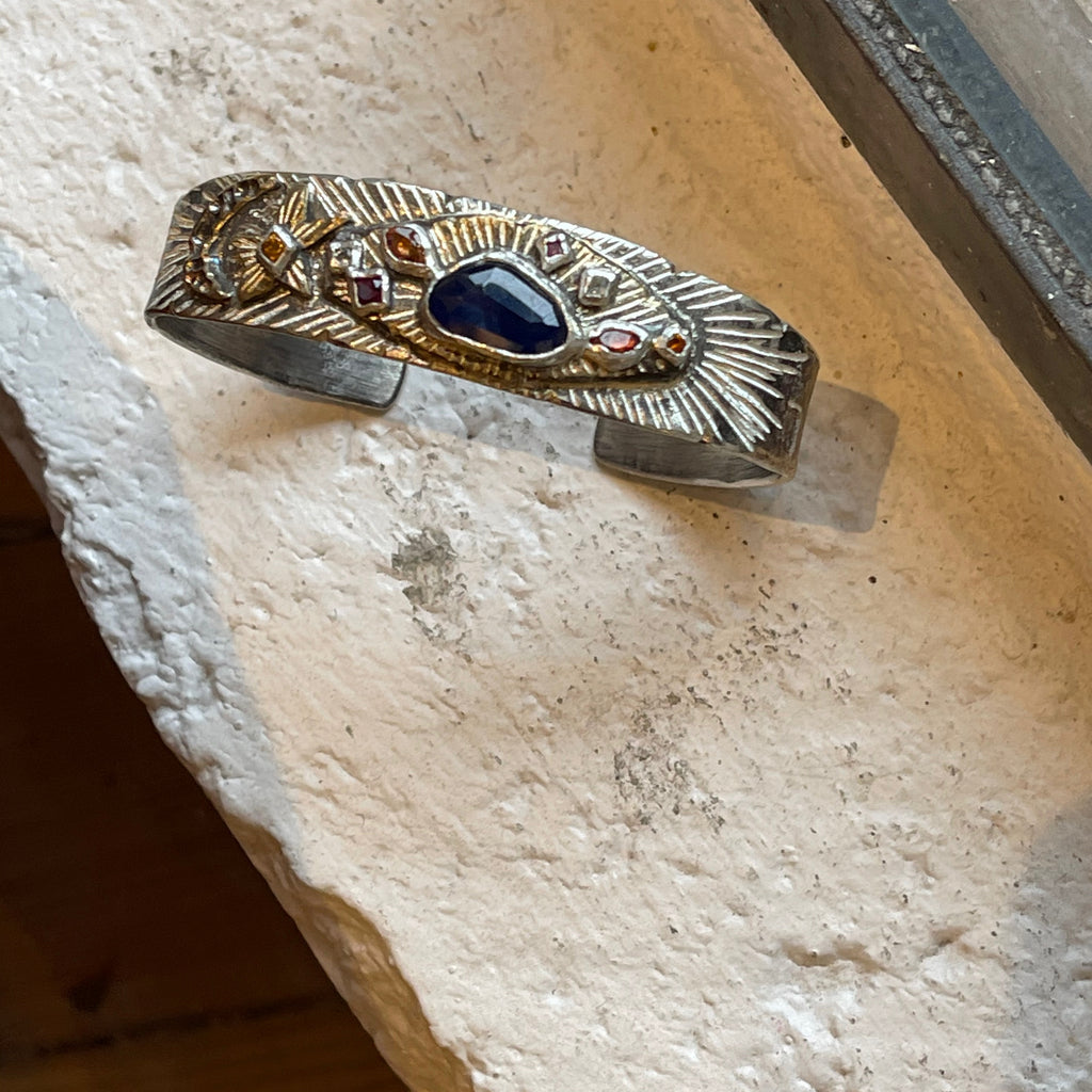 An absolute stunner on your wrist. Wear this unisex cuff by Franny E on its own or layer it for dramatic emphasis. It's hand-formed of fine silver, bronze, and a natural ethically sourced lapis center, citrine, sapphire and aquamarine.