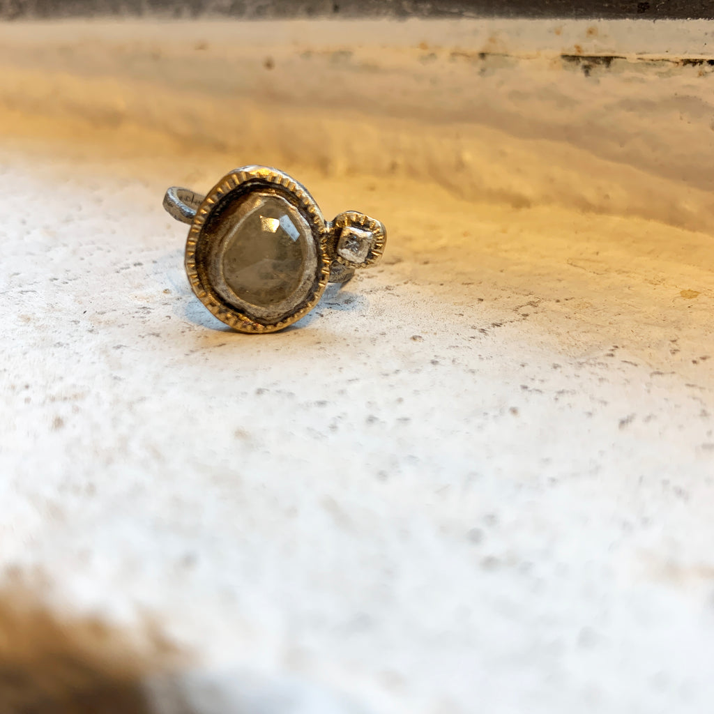 The reflection in an echo is interpreted by Franny E here in this beautiful 2-stone ring. A faceted cabochon pale yellow sapphire with the echo as a diamond next to the gem. 14K gold and fine silver.