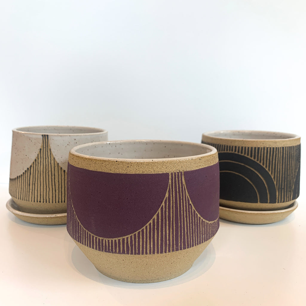 Judith's wheel thrown planters create mix and match delight with their geometric designs and fresh style. Group in purple, black and cream.