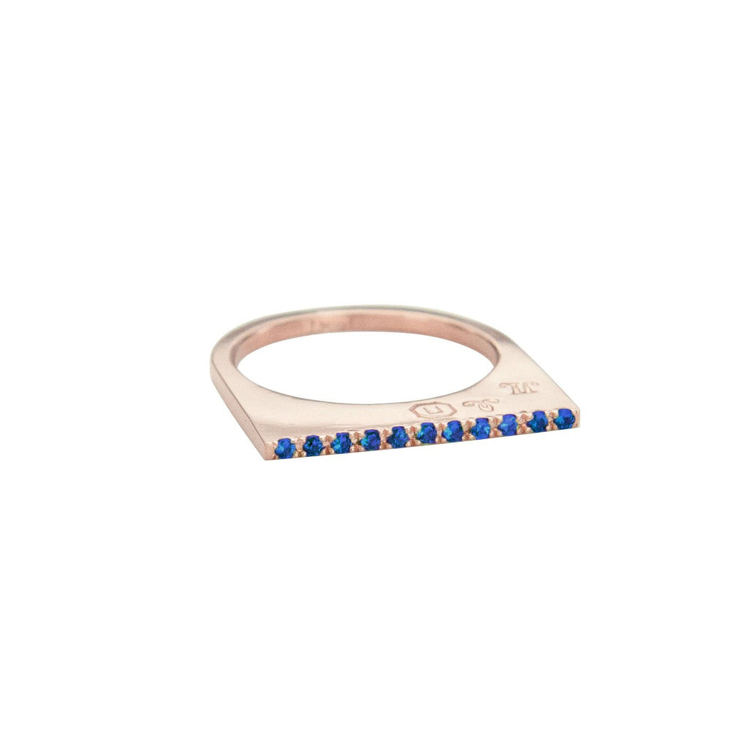 Add dramatic height and sparkle to your stacking rings with Jeffrey Levin's super flat skinnys encrusted in diamonds or colorful gems. Inspired by beautiful bon bon desert plating, Jeffrey Levin designed a unique proportion and stunning surface in 14k rose gold with pave set blue sapphires.