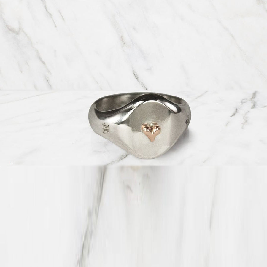Jeffrey reimagines the classic Signet Ring, reworking it with feminine lines and using it as a canvas for other pretty things, like this contrasting tiny heart charm adornment in 14K rose gold.