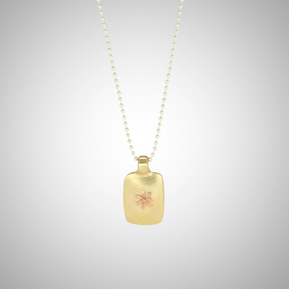 Jeffrey reimagined the classic dog tag into a modern canvas, both refined and a bit edgy. He loves mixing metals and embellished this 14k yellow gold dog tag with a contrasting 14K rose gold tiny flower charm