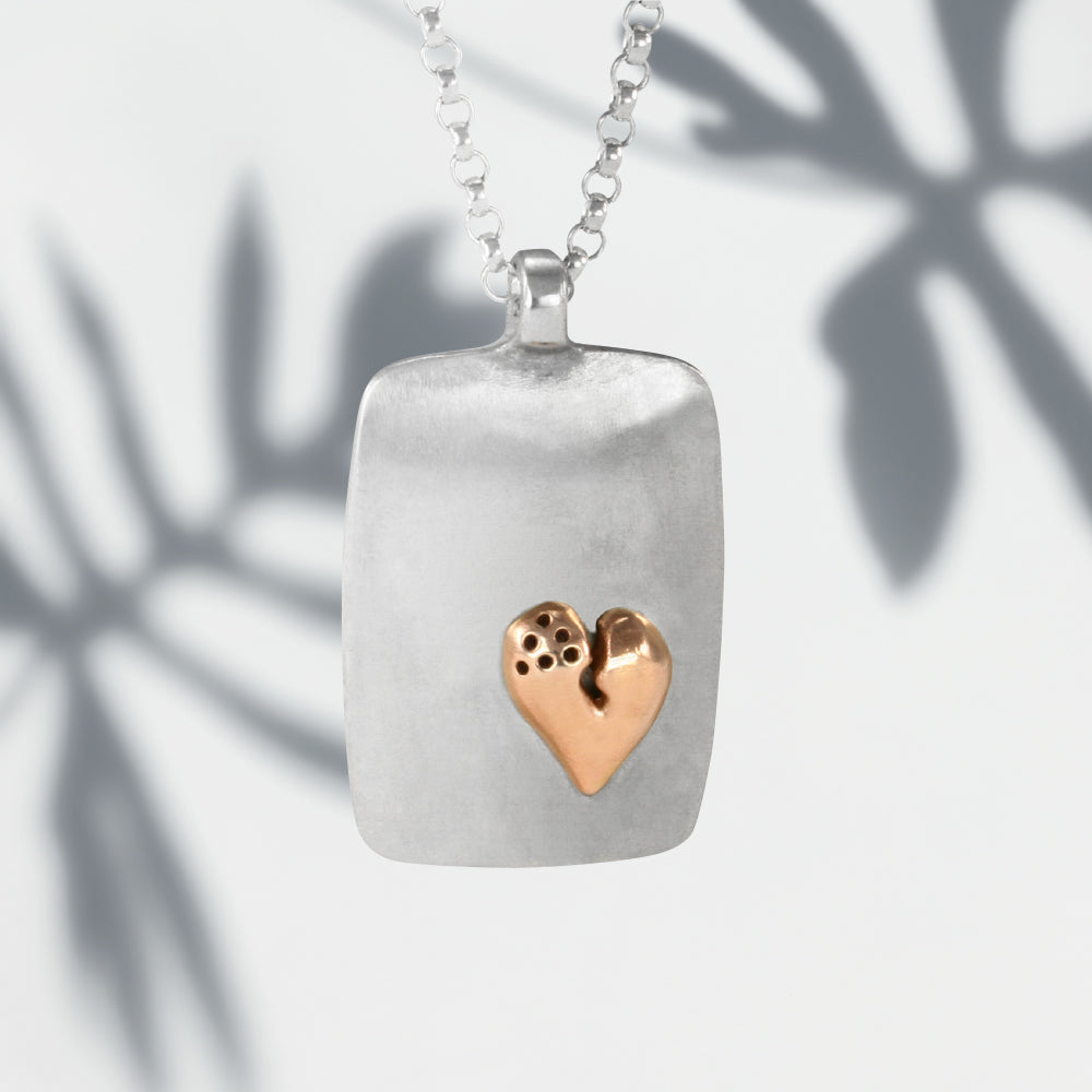 Jeffrey reimagined the classic dog tag into a modern canvas, both refined and a bit edgy. He loves mixing metals and adorned this large sterling silver dog tag with a contrasting 14K rose gold healed heart pendant from his signature collection.