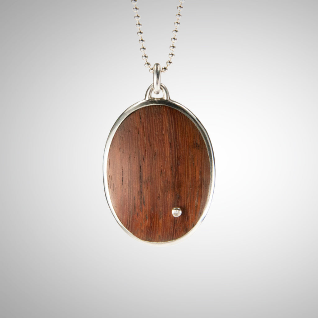 Jeffrey expands his wood collection with a stunning statement necklace using reclaimed wood, gorgeously reused. He cuts the wood to best feature the beauty of the graph lines, from creamy brown to pink-brown. He also makes a setting for a single diamond and pins it through the wood, while setting the two in a large oval sterling setting on chain.
