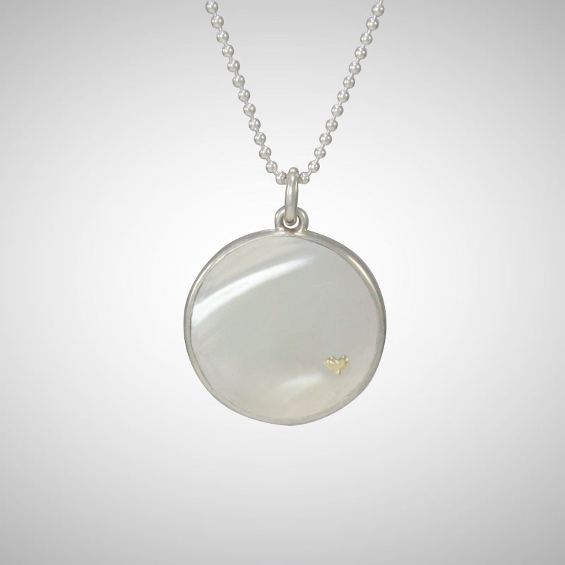 We love the luminescent white mother of pearl pendant embellished with Jeffrey's signature tiny 14K yellow gold heart charm, pinned through the shell.