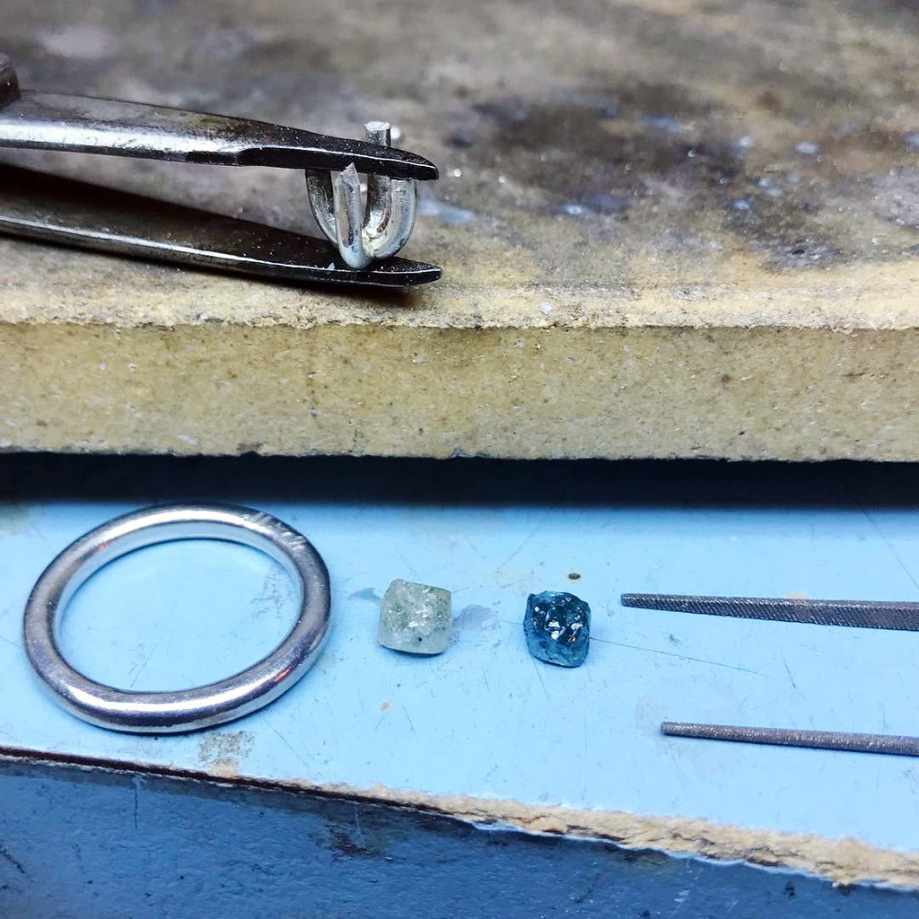 Rough diamond ring settings and rough diamonds in the process of production.