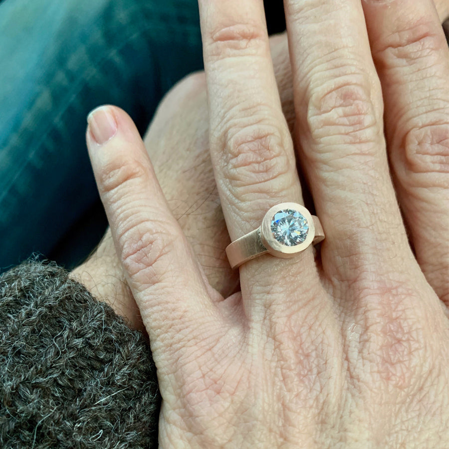 The custom engagement ring designed by Jeffrey Levin has been carved in wax, cast in rose gold and features and stunning diamond. Shown on bride's hand.